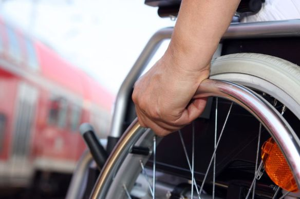 A shot of a wheelchair from a low angle with a train in the background.