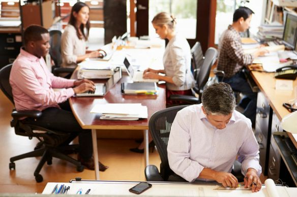 Office environment with focus on man working in foreground