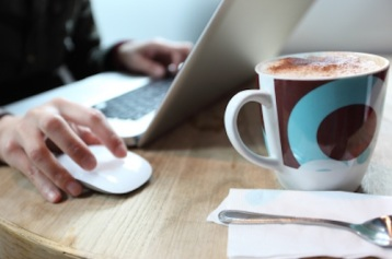 home-worker-image-obscured-person-using-a-laptop-with-mug-of-coffee