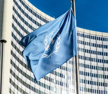 Image of UN flag with headquarters in the background