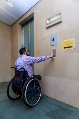 Man in a wheelchair calling an elevator