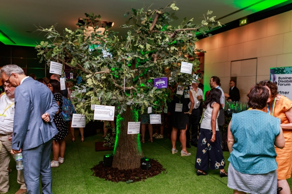 An indoor tree with people around it at the Partner Group Reception