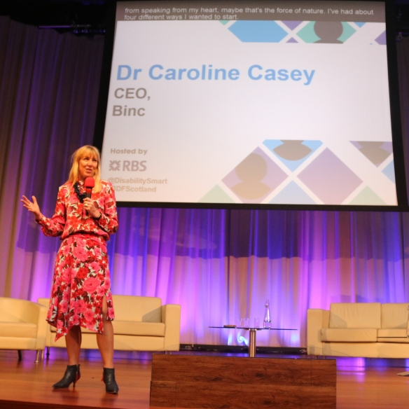 "Dr Caroline Casey on stage with a slide that says: ""Dr Caroline Casey CEO, Binc"""
