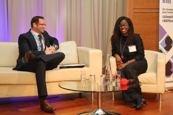 Business Disability Consultants Adrian Ward (left) and Ruth Fisher (right) on the stage - they are smiling