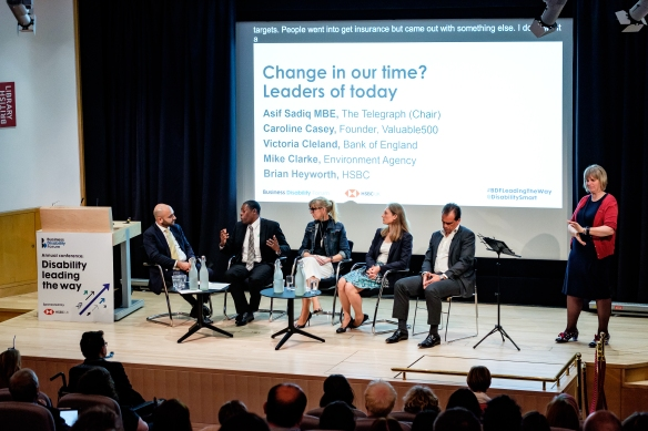 On the stage is the Change in our time? Leaders of today panel with Asif Sadiq ME, Mike Clarke, Caroline Casey, Victoria Cleland, Mike Clarke and Brian Heyworth and a BSL interpreter.