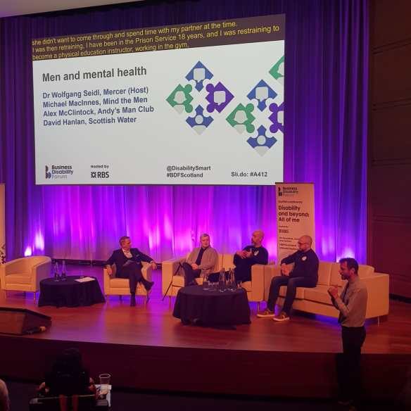 Dr Wolfgang Seidl (pictured left), David Hanlan (pictured second left), Alex McClintock from Andy's Man Club (pictured second right) and Michael MacInnes from Mind the men (pictured right) on stage. There is also a BSL interpreter in front of the stage.